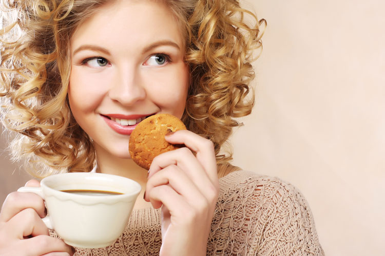 Smiling young woman with tea and cookie