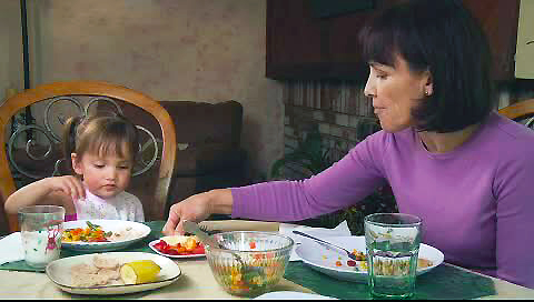 Grandmother fussing and arranging granddaughter's food