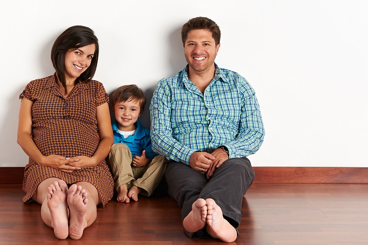 Pregnant family mom dad little boy smiling happily