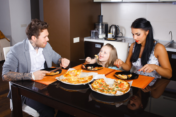 Parents and little girl sitting looking at each other enjoying pizza