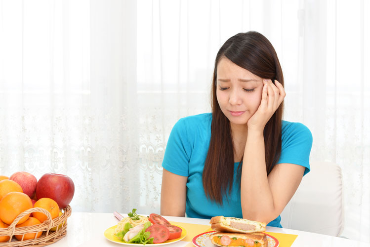 Young woman looking upset at mealtime