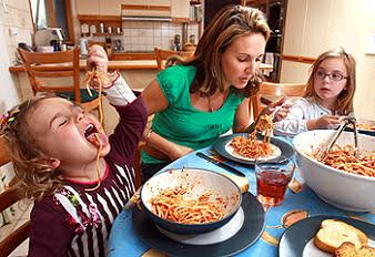 Preschooler making a mess sharing spaghetti with family