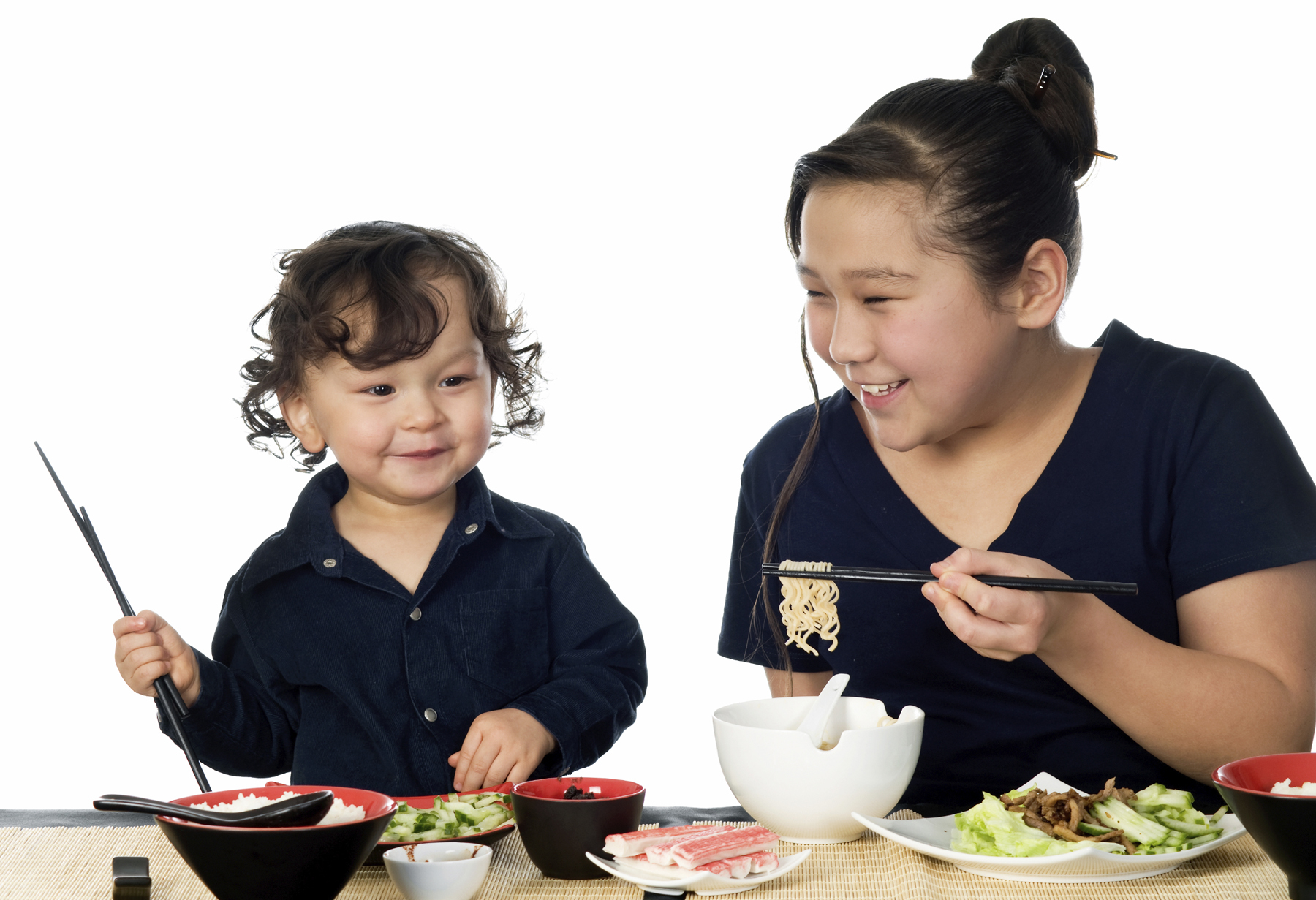 Preschool boy and mother enjoy eating a meal with chopsticks